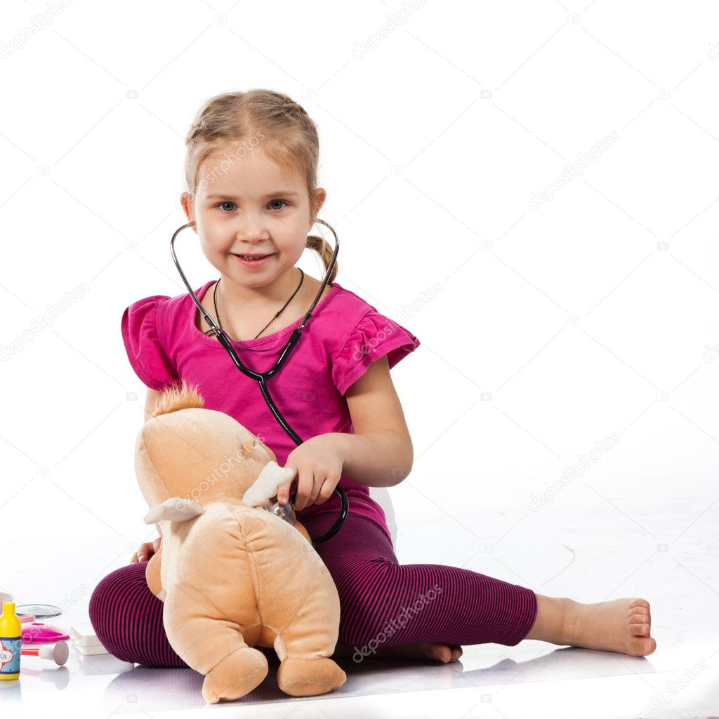 Beautiful girl playing doctor with a doll isolated on white — Stock Photo #4835333