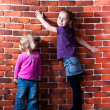 Children posing near the brick wall — Stock Photo