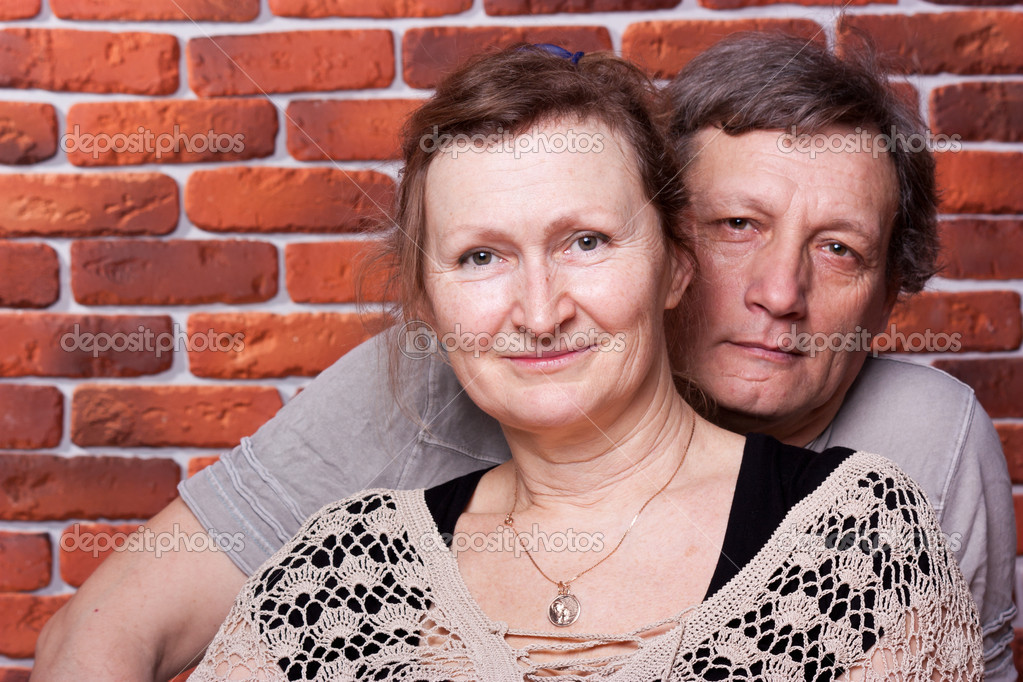 Happy seniors couple in love against brick wall  Stock Photo #5102149