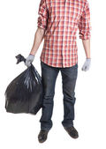 Man holding black plastic trash bag in his hand — 图库照片