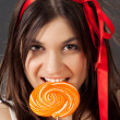 Royalty-Free Stock Photo: Beautiful girl bites lollipop