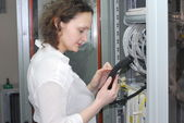 Woman working on telecommunication equipment — Stock Photo