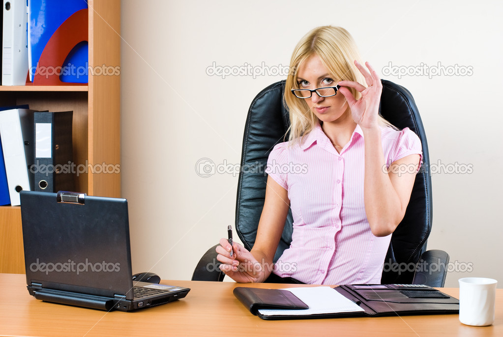 Business woman working on a laptop at the office and smiling — Stock Photo #4265173