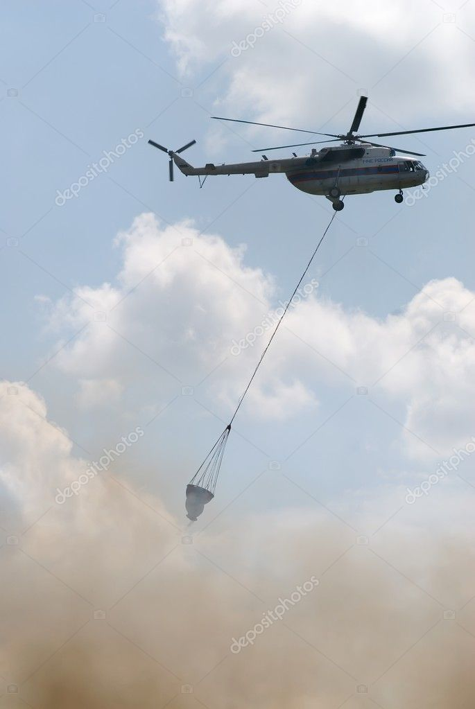 Firefighter helicopter MI-8 with water tank over fire — Stock Photo #4291839