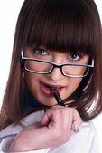 Girl biting pen — Stockfoto