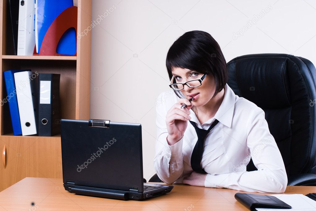 Business woman working on a laptop at the office and smiling — Stock Photo #4842412