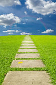 Walking stone on grass to sky and rainbow — Stock Photo