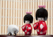 Two small Japanese dolls and small elephant — Stock Photo