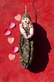 Cloth doll hanging on red wall with heart symbol note stick — Stockfoto