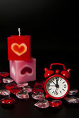 Two candles with red clock isolated on black background — Stock Photo