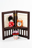 Japanese doll and orange clock on flower stand — Stock Photo