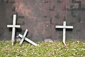 Three wooden crosses lean on the wall — Stock Photo