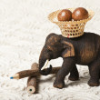 Wooden elephant carry nut in the basket — Stock Photo
