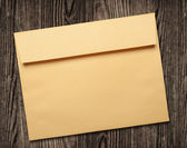 Golden envelope on wooden table. — Stock Photo