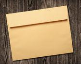 Golden envelope on wooden table. — Stock Photo