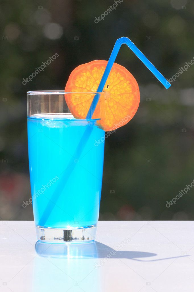 Glass of blue drink with straw and slice of an orange for Orange and blue cocktails