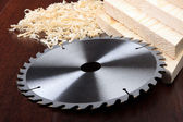 Circ saw blades, planks and shavings on dark background — Stock Photo