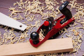 Red plane, wooden brick, handsaw and shavings — Stock Photo