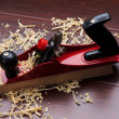 Red plane on brick and shavings. — Stock Photo
