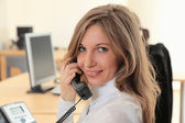 Young girl at office on the workplace makes call — Stock Photo
