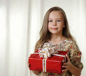 Little girl holds a red box with a gift — Stock Photo