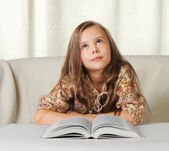 Little girl dreams when reading the book — Stock Photo