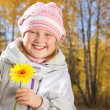 Portrait of smiling little girl with a yellow flower in the autumn forest. — Stock Photo