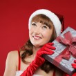 Young charming girl dressed as Santa holds a gift in the form of heart in h — Stock Photo