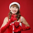 Young charming girl dressed as Santa holds a gift in the form of heart in h — Stock Photo #4388547
