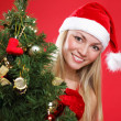 The young beautiful girl dressed as Santa and a christmas fur-tree — Stock Photo
