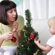 Mum and her small daughter decorate a christmas fur-tree — Stock Photo