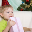 Little boy near to christmas fur-tree sits with gift — Stock Photo