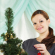 The young beautiful woman decorate a christmas fur-tree — Stock Photo #4388673