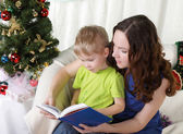 Mum reads to the son the book near a christmas fur-tree — Stock Photo