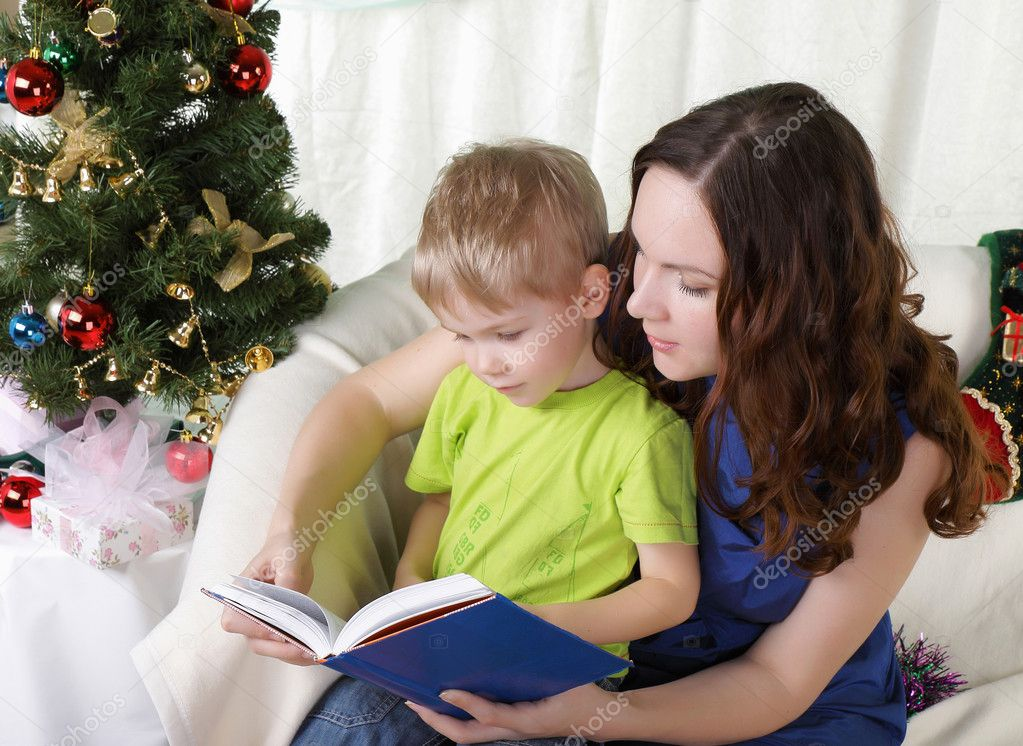 Mum reads to the son the book near a christmas fur-tree  Stock Photo #4388647