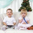 Kids playing near to christmas fur-tree — Stock Photo
