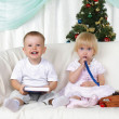 Kids playing near to christmas fur-tree - Stock Photo