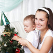 Mum and her son decorate a christmas fur-tree — Stock Photo