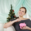 Stock Photo: The young beautiful woman decorate a christmas fur-tree