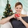The young beautiful woman decorate a christmas fur-tree — Stock Photo