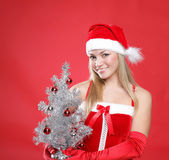 Girl dressed as Santa and a christmas fur-tree — Stock Photo