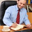 Stock Photo: Businessman at office working at his workplace.