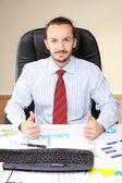 Affärsman på sin arbetsplats hålla tummen upp. — Stockfoto