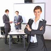 Portrait of business woman with team mates discussing in the background — Stock Photo