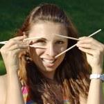 Beautiful girl hold chopsticks near eyes — Stock Photo