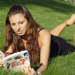 Girl reading and lying on grass — Stock Photo #3977378