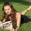 Girl reading and lying on grass - Stock Photo