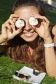 Beautiful girl hold rolls or sushi near eyes funny — Stock Photo