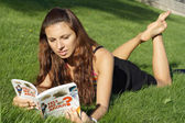 Girl reading and lying on grass — Stock Photo