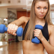 Girl hold dumbbells in hand with strong abdomen — Stock Photo #4339429